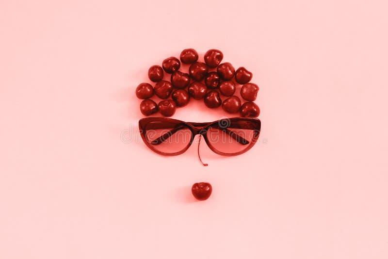 Den röda söta körsbäret lade ut i bild av kvinnan i solglasögon med kanter på rosa bakgrund, tonad korall Begreppsungdom, skönhet royaltyfri foto