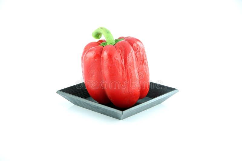 Den röda spanska pepparen i den svarta maträtten. arkivfoton