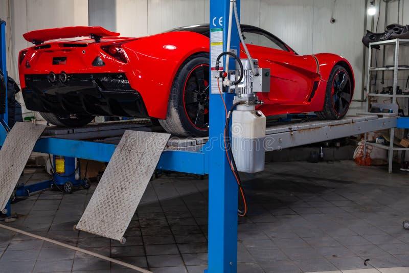 Den röda sportbilen som lyfts på en elevator i en bilreparation, shoppar, den bakre stötdämparen och spoiler arkivfoton