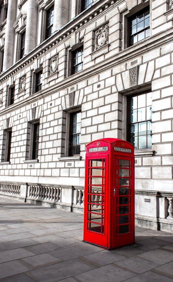 Den röda telefonasken i London, Förenade kungariket, baksidan är byggnaden arkivfoton