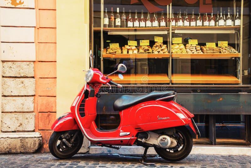 Den röda Vespasparkcykeln parkerade framme av bagerit i Rome, Italien royaltyfri bild