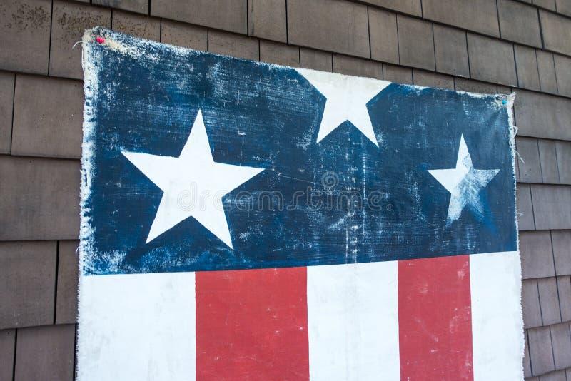 Den röda vita blåa flaggan med tre stjärnor som sörjas till en outsited träväggamerikan, semestrar den juli fjärdedelen royaltyfri bild