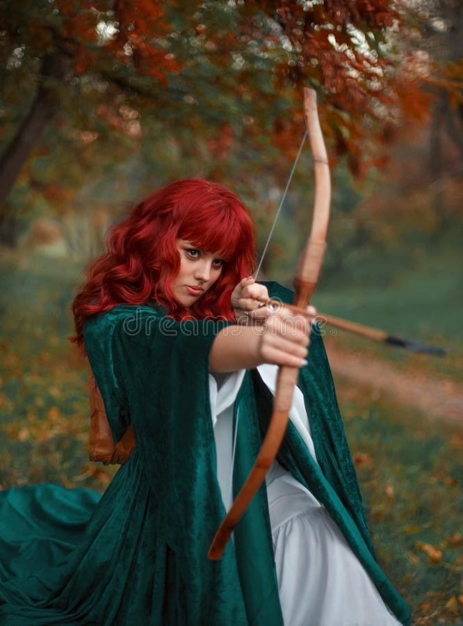 Den rödhåriga brännheta rånaren i ögonblick för attack, legenden av Robin Hood, flicka rymmer en pilbåge och en pil i hennes händ royaltyfria bilder
