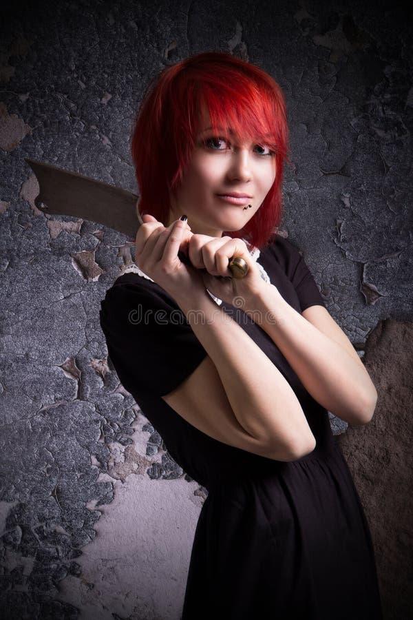 Den rödhåriga flickan har en yxa fotografering för bildbyråer
