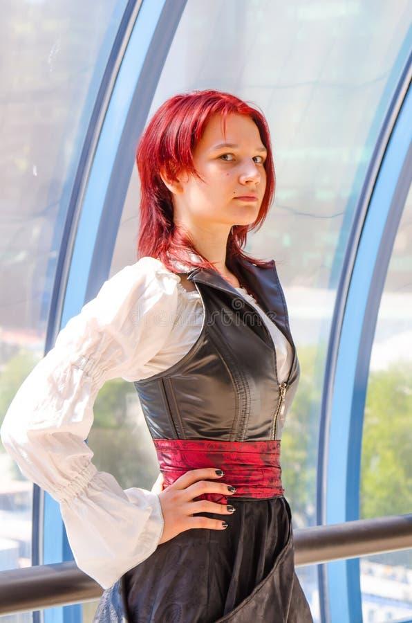 Den rödhåriga flickan i en lång klänning går på bron royaltyfri fotografi