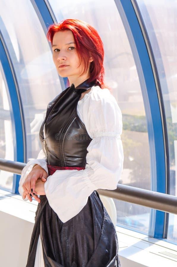 Den rödhåriga flickan i en lång klänning går på bron royaltyfri foto