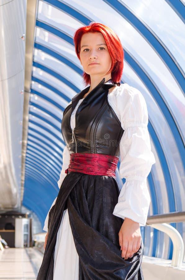 Den rödhåriga flickan i en lång klänning går på bron arkivbilder
