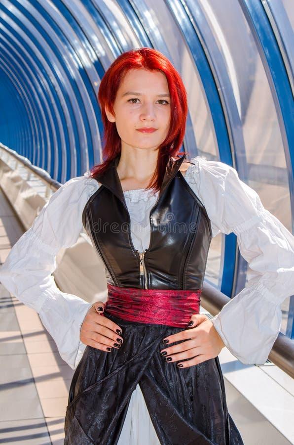 Den rödhåriga flickan i en lång klänning går på bron fotografering för bildbyråer
