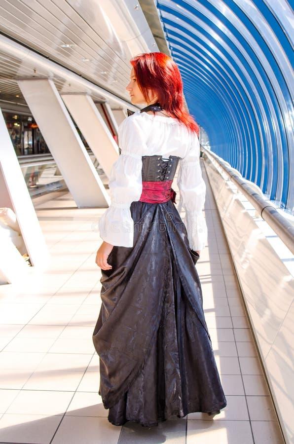 Den rödhåriga flickan i en lång klänning går på bron arkivfoto
