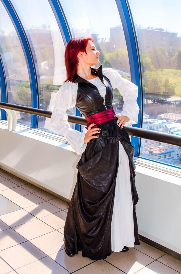 Den rödhåriga flickan i en lång klänning går på bron royaltyfri bild