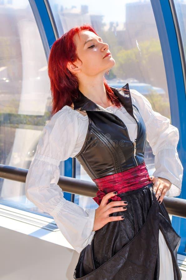 Den rödhåriga flickan i en lång klänning går på bron arkivbild