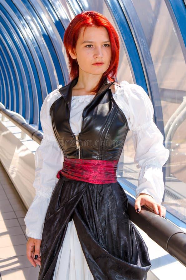 Den rödhåriga flickan i en lång klänning går på bron arkivfoton