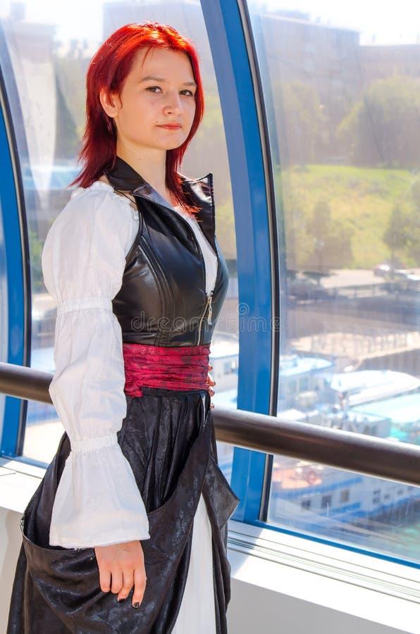 Den rödhåriga flickan i en lång klänning går på bron royaltyfria foton