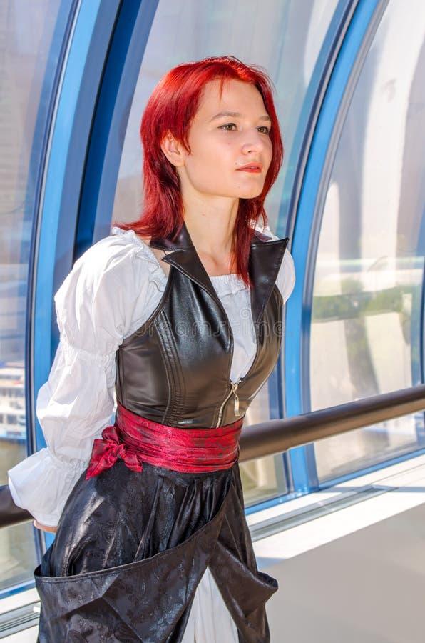 Den rödhåriga flickan i en lång klänning går på bron royaltyfria bilder