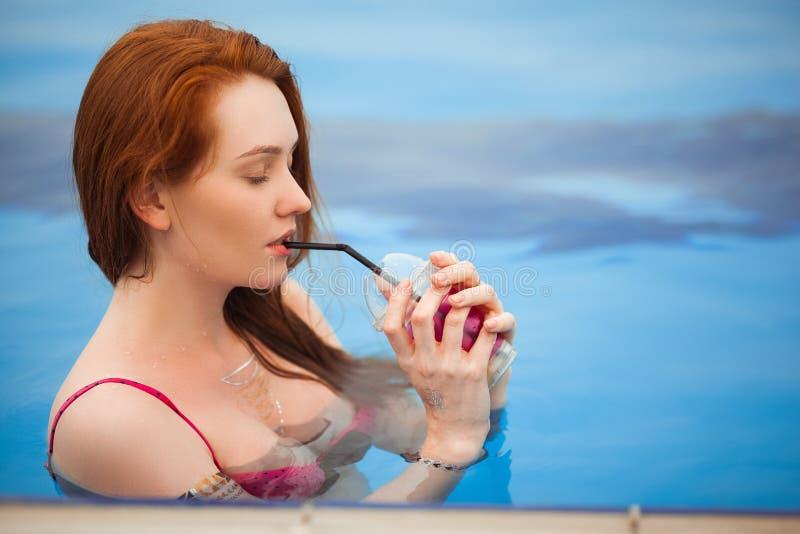 Den rödhåriga flickan i ett baddräktanseende i en pöl I händerna som rymmer ett exponeringsglas av kall orange fruktsaft royaltyfri bild