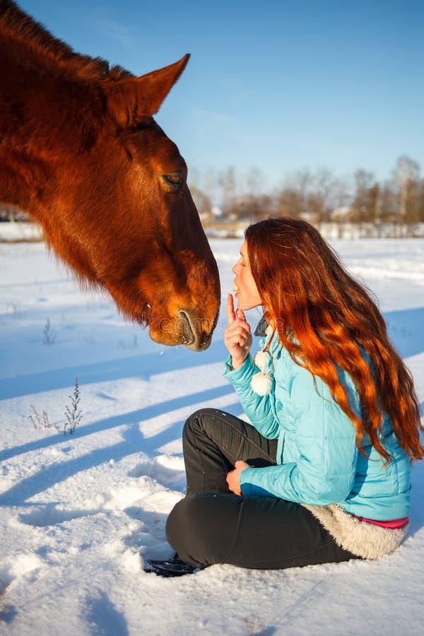 Den rödhåriga flickan i ett snöig fält matar ett äpple från händer arkivfoton