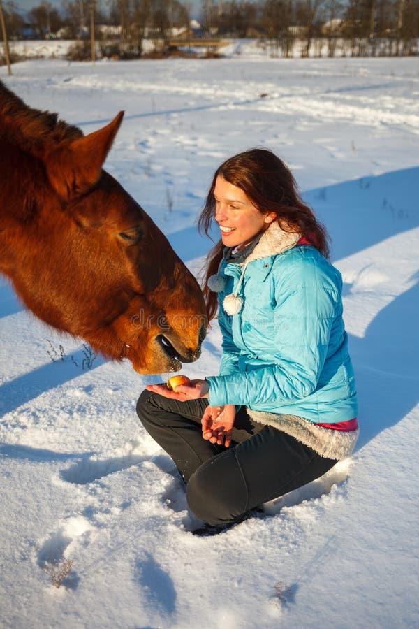 Den rödhåriga flickan i ett snöig fält matar ett äpple från händer arkivbilder
