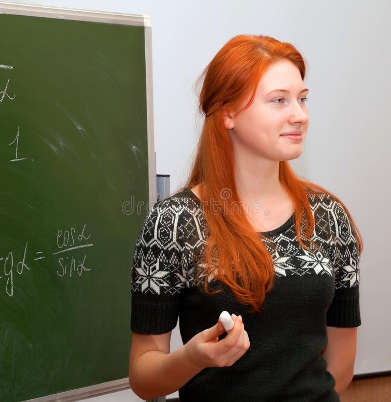 Den rödhåriga flickan i mathgrupp royaltyfri foto