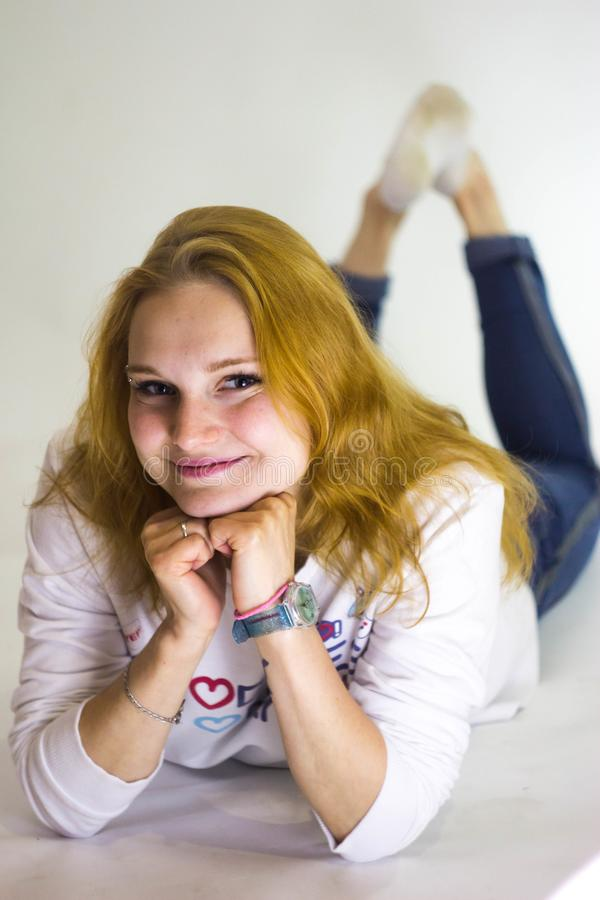 Den rödhåriga flickan ligger och ler på kameran arkivbild