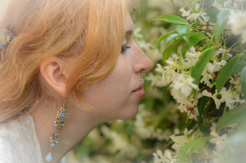 Den rödhåriga flickan luktar de vita blommorna royaltyfria bilder
