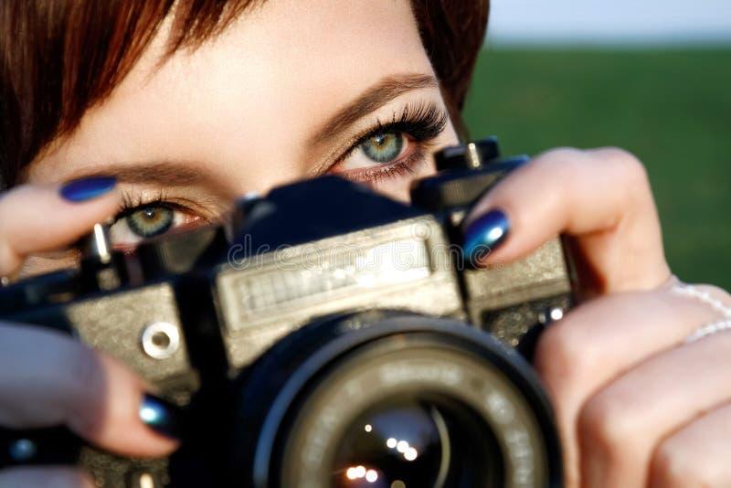 Den rödhåriga flickan med gröna ögon som fotograferas i stad, parkerar arkivfoto
