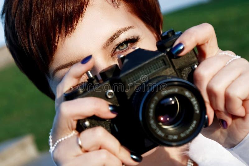 Den rödhåriga flickan med gröna ögon som tar bildkameran i staden, parkerar fotografering för bildbyråer