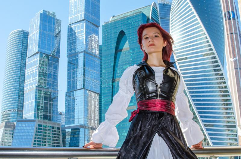 Den rödhåriga flickan står på bron på bakgrunden av höghus royaltyfria bilder