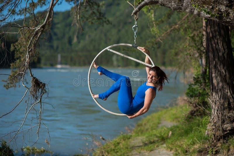 Den rödhåriga gymnasten i en blå dräkt som gör de svåra övningarna på luften, ringer i natur royaltyfri fotografi