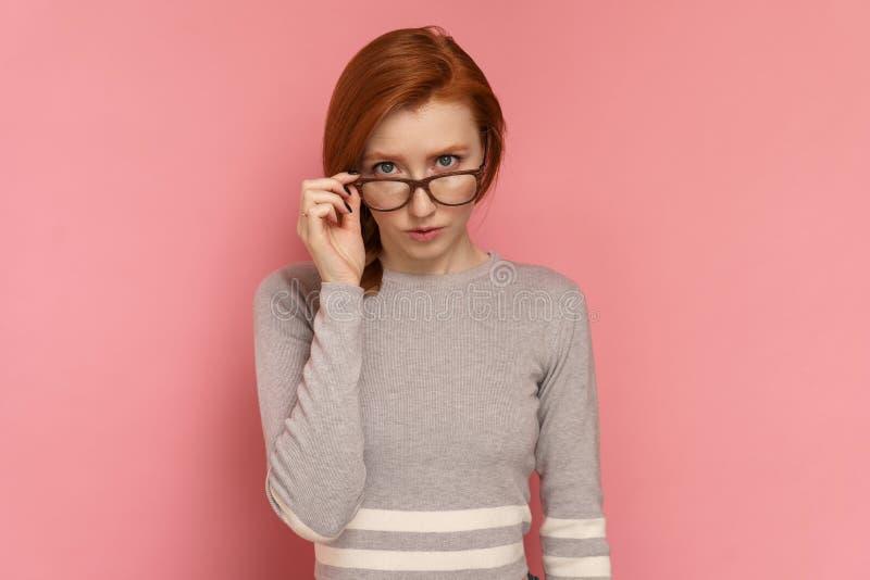 Den rödhåriga unga kvinnan ser fast beslutsamt på kameran till och med exponeringsglasen arkivfoton