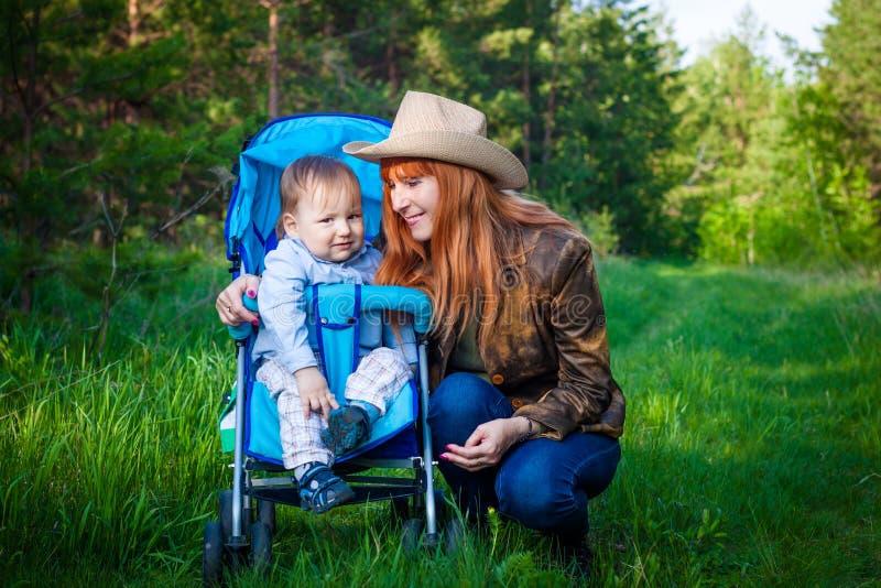 Den rödhåriga unga le farmodern går med hennes två-år-gamla sonson i sommaren i skogen fotografering för bildbyråer