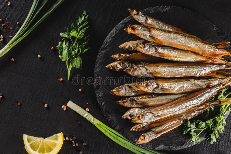Den rökte fisklilla stackaren som marineras med kryddor, saltar, gräsplaner, och skivan av bröd på plattan över mörker stenar bak fotografering för bildbyråer