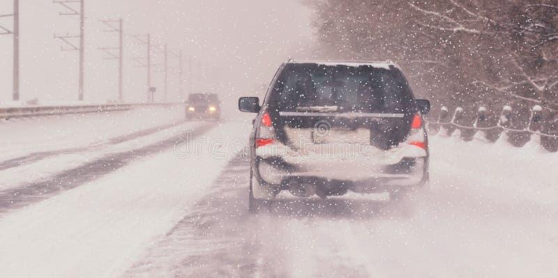 Den rörande bilen på den snöig vintervägen bland djupfryst skog efter regnar snöslask Kallt väder, snöstorm, dålig synlighet, hal royaltyfria foton
