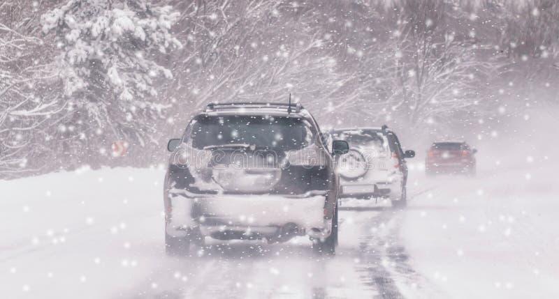 Den rörande bilen på den snöig vintervägen bland djupfryst skog efter regnar snöslask Kallt väder, snöstorm, dålig synlighet, hal arkivfoton