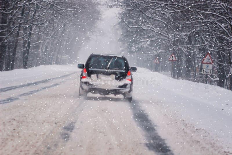 Den rörande bilen på den snöig vintervägen bland djupfryst skog efter regnar snöslask Kallt väder, snöstorm, dålig synlighet, hal fotografering för bildbyråer