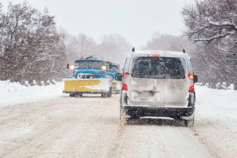 Den rörande bilen på den snöig vintervägen bland djupfryst skog efter regnar snöslask Kallt väder, snöstorm, dålig synlighet, hal royaltyfri foto