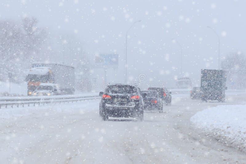 Den rörande bilen på den snöig vintervägen bland djupfryst skog efter regnar snöslask Kallt väder, snöstorm, dålig synlighet, hal arkivbild