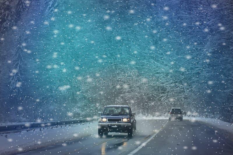 Den rörande bilen på den snöig vintervägen bland djupfryst skog efter regnar snöslask Kallt väder, snöstorm, dålig synlighet, hal royaltyfri bild