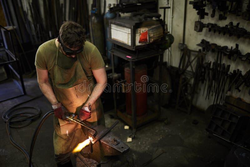 Den rörande facklan, medan bitande, belägger med metall arkivfoto