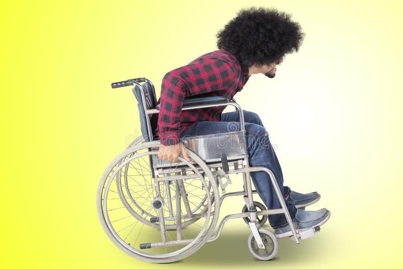 Den rörelsehindrade afro- mannen går med rullstolen på studio fotografering för bildbyråer