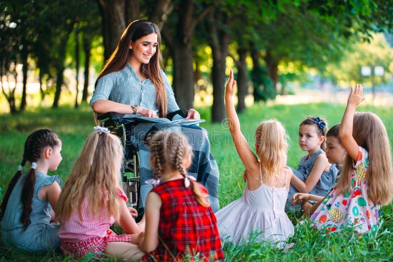 Den rörelsehindrade läraren för en kurs med barn i natur Växelverkan av en lärare i en rullstol med studenter fotografering för bildbyråer