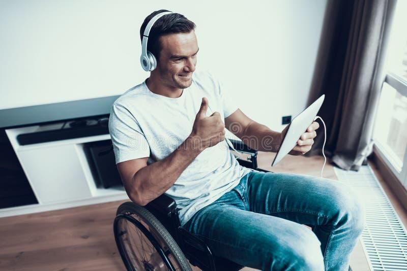 Den rörelsehindrade mannen i hörlurar meddelar via minnestavlan royaltyfria bilder