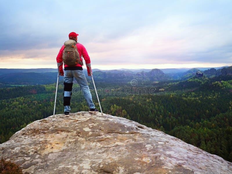 Den rörelsehindrade mannen med kryckor står på ett stort vaggar och se till berg på horisonten arkivbilder