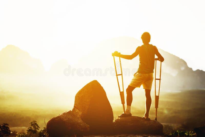 Den rörelsehindrade mannen står kryckabergbakgrunden fotografering för bildbyråer