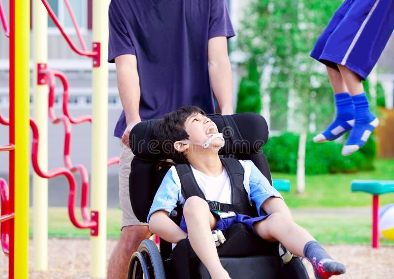 Den rörelsehindrade pojken i rullstol som tycker om hålla ögonen på vänner, spelar på medeltalen royaltyfri foto