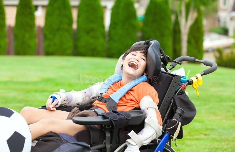 Den rörelsehindrade pojken i rullstolen som spelar med fotbollbollen på, parkerar royaltyfria foton