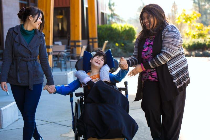 Den rörelsehindrade pojken i rullstolinnehavhänder med anhörigvårdare går på arkivfoto