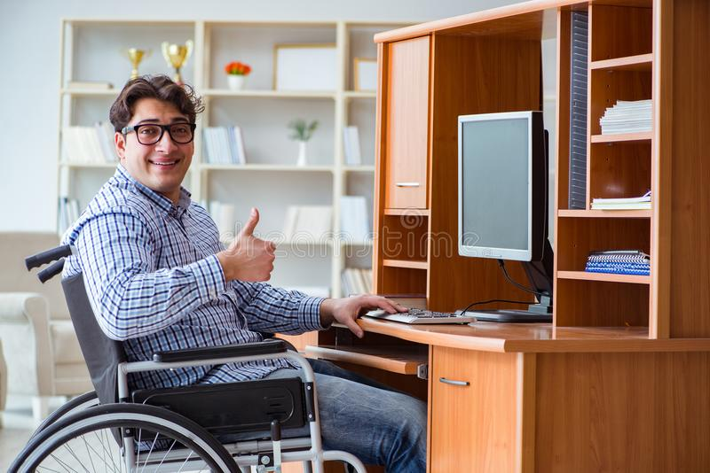 Den rörelsehindrade studenten som hemma studerar på rullstolen royaltyfri foto