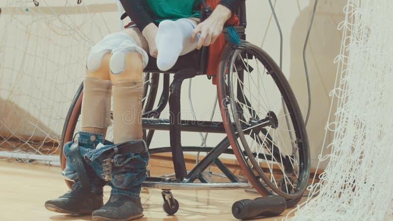 Den rörelsehindrade unga sportive mannen med protes av ben transplanterade till rullstolen för sportive utbildning royaltyfri fotografi