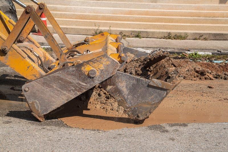 Den rörmokerireparationsmannen och grävskopan kammar hem att gräva, reparation av röret royaltyfri bild