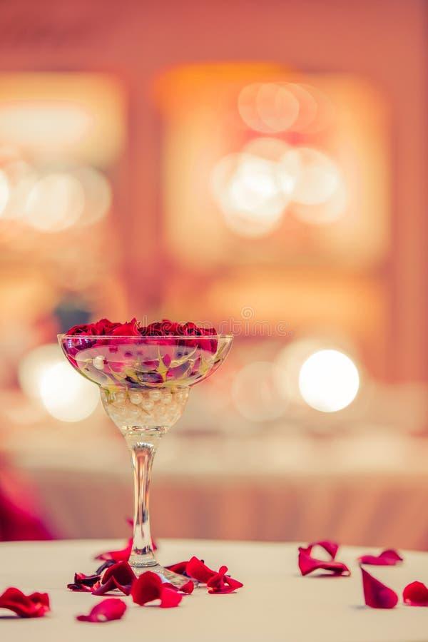 Den r?da rosknoppen ligger i ett exponeringsglas av champagne royaltyfri foto